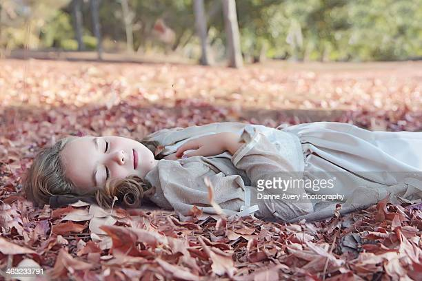 sleeping beauty - girl laying in leaves - sleeping beauty stock photos and pictures