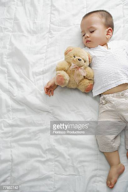 Sleeping boy with teddy bear on bed