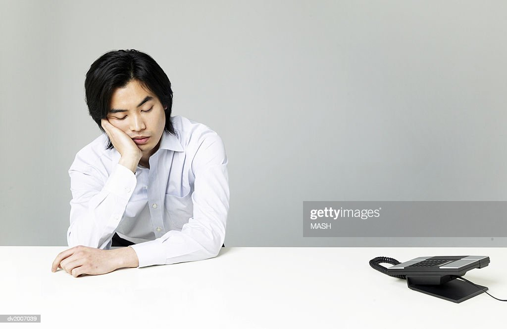 Sleeping Businessman With His Hand on His Chin Sitting by a Telephone : Stock Photo