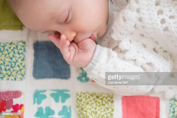 Sleeping Caucasian baby sucking thumb