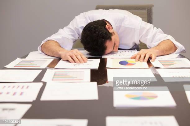 Sleeping Caucasian businessman laying on paperwork