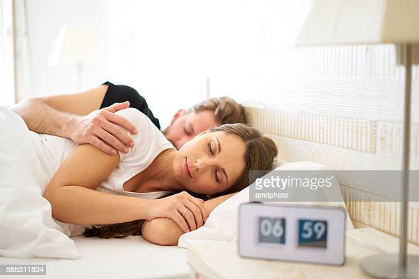 sleeping couple with blurred alarm clock before wakeup call