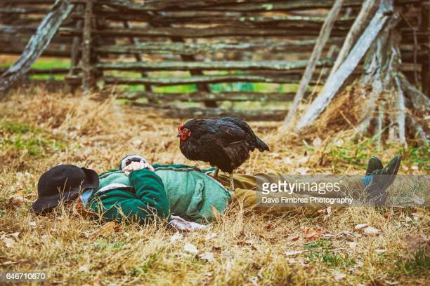sleeping figure with rooster on top - funny rooster stock photos and pictures