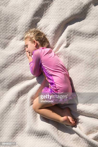 sleeping girl curled up on a bed - fetal position stock photos and pictures