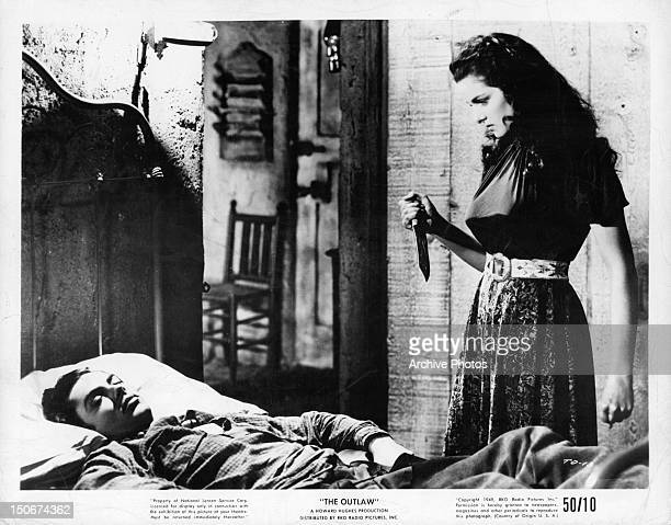 A sleeping Jack Buetel is approached by knife wielding Jane Russell in a scene from the film 'The Outlaw' 1949