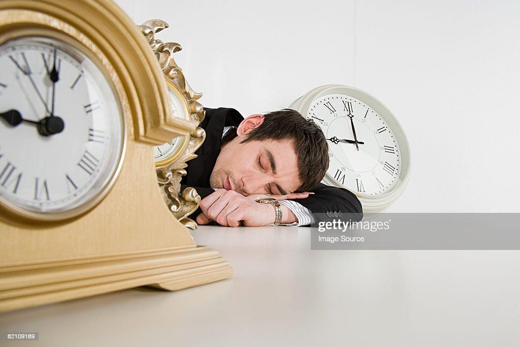 Sleeping man and clocks : Stock Photo