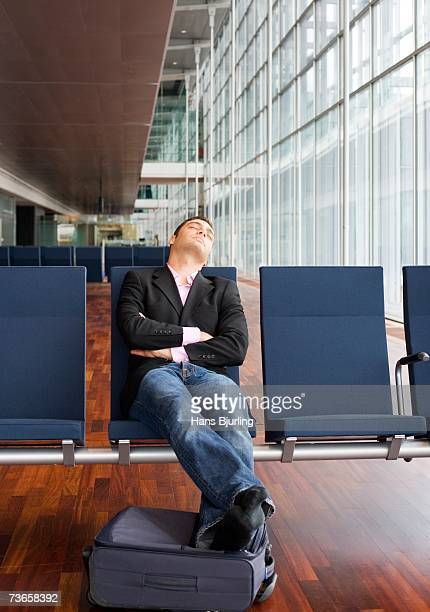 a sleeping man in an airport. - one man only stock pictures, royalty-free photos & images