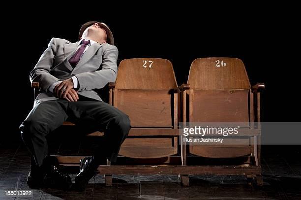 A sleeping man inside a theater house