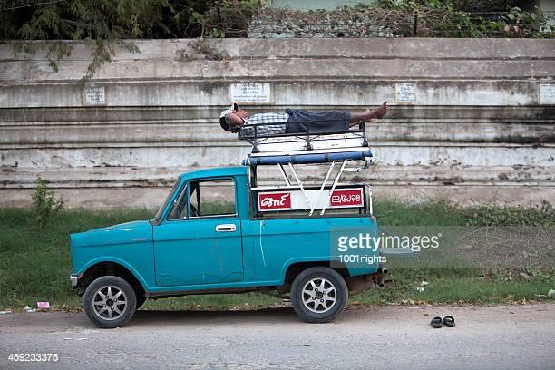 sleeping man, myanmar - luggage rack stock photos and pictures