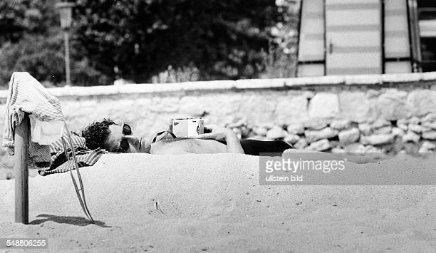 sleeping man on the beach 1960 Photographer Jochen Blume Vintage property of ullstein bild