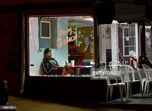 CONTENT] A sleeping man seen through the window of a corner pizza place in Baltimore Maryland during the Christmas Holidays I'm not sure if he was...