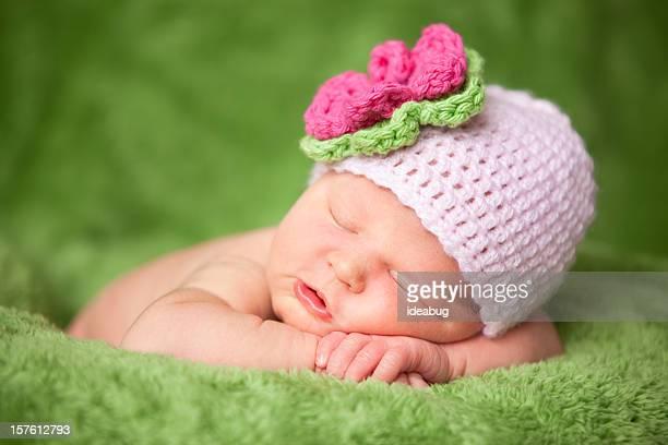 Schlafen neugeborene Baby Mädchen tragen gestrickte Mütze mit Blume