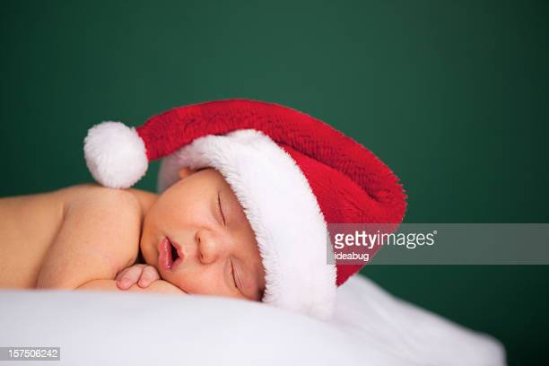 Sleeping Newborn Baby Wearing Santa Hat for Christmas