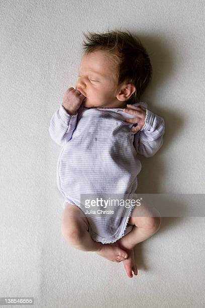 A sleeping newborn sucking on her fist