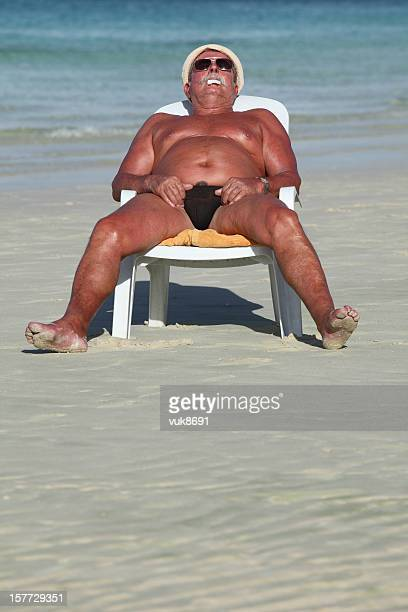 sleeping on the beach - fat man on beach stock photos and pictures
