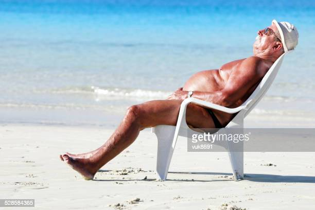 sleeping on the beach - chubby swimsuit stock photos and pictures
