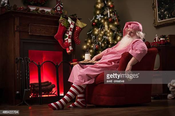 Schlafen Santa im Sofa mit Milch und Kekse
