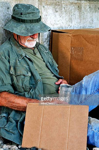 sleeping vet with blank sign and a tin can - homeless veterans stock photos and pictures