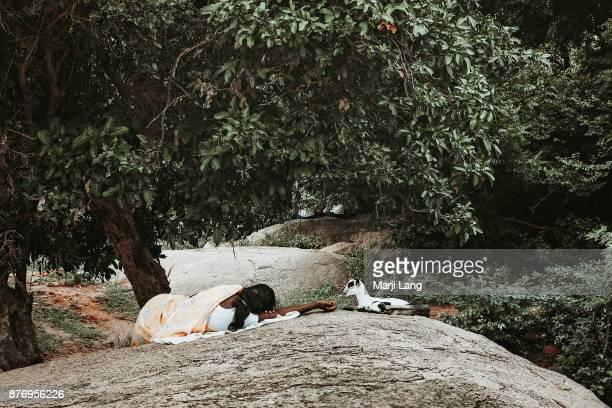 Sleeping woman with baby goats in Mamallapuram Tamil Nadu India