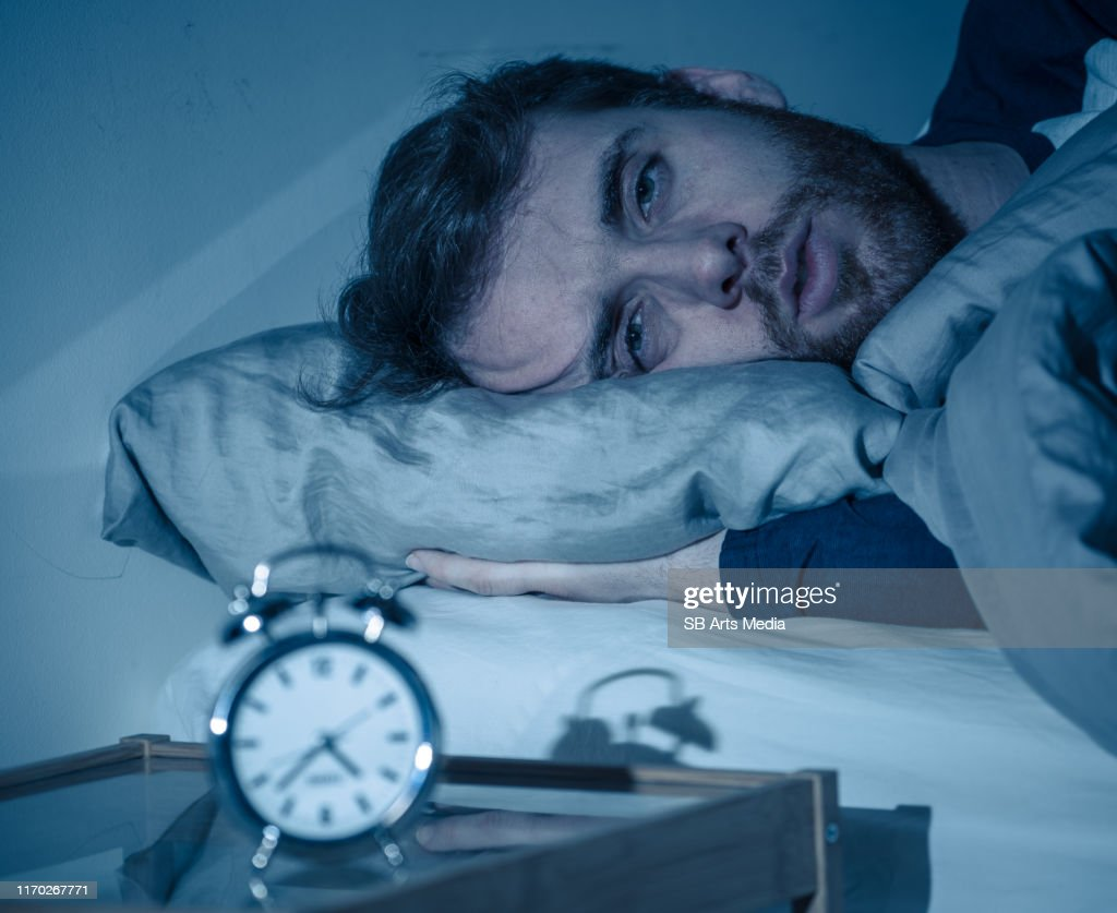 Sleepless and desperate young caucasian man awake at night not able to sleep, feeling frustrated and worried looking at clock suffering from insomnia in stress and sleeping disorder concept. : Stock Photo