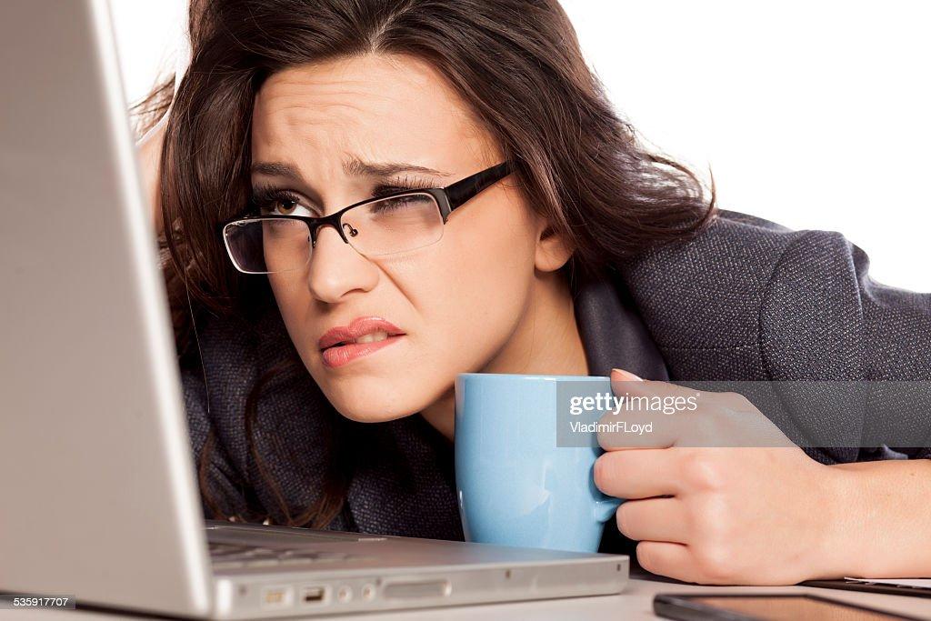 Sleepy y cansado mujer de negocios con computadora portátil, con un café : Foto de stock