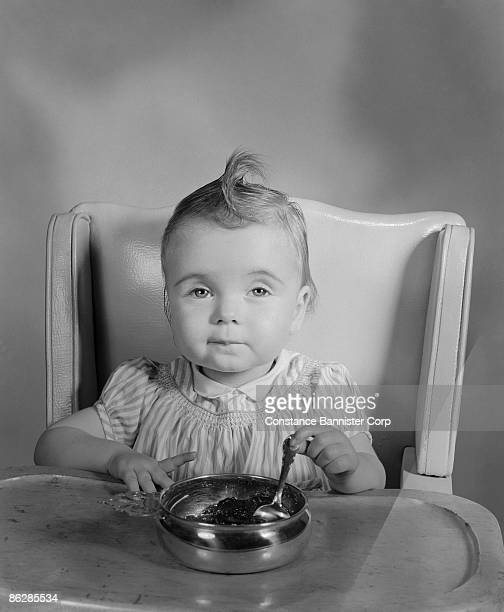 Sleepy baby sitting in high chair with bowl of food