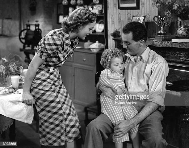 A sleepy Binkie Stuart gets a cuddle from John Longden in a scene with Kathleen Kelly from the film 'Little Miss Somebody' a vehicle for the rise to...