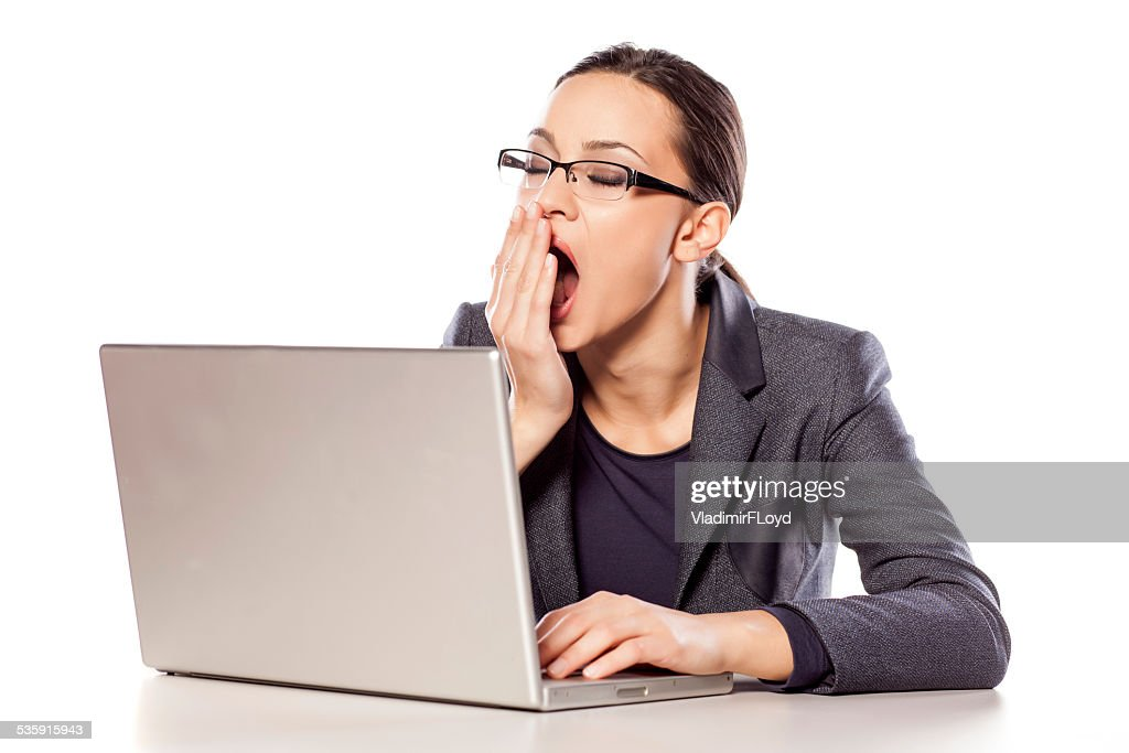 Sleepy business woman sitting at the desk with a laptop : Stock Photo