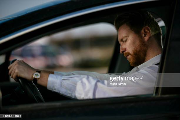 sleepy businessman driving car - tired stock pictures, royalty-free photos & images