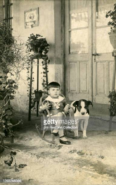 A sleepy dog stands next to a boy in a rocking chair surrounded by house plants circa 1917