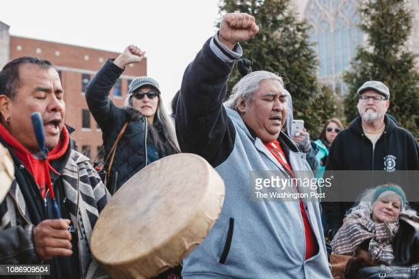 Sleepy Eye LaFromboise beat a drum chanted and prayed while Corine Fairbanks center and Albert Ortiz held their fists in the air at a protest outside...