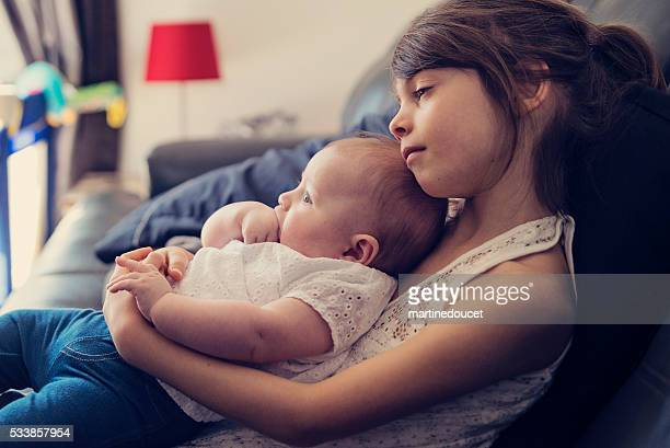 """sono de menina segurando bebê irmã no sofá em casa. - """"martine doucet"""" or martinedoucet imagens e fotografias de stock"""
