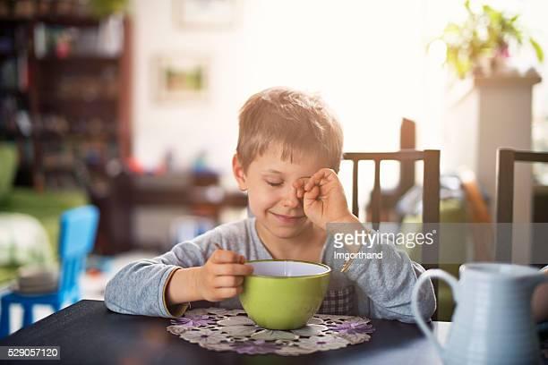 Sleepy little boy eating breakfast cereal