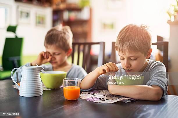 Verschlafenen kleinen Jungen Essen Frühstück mit Zerealien