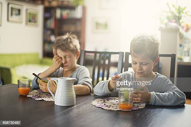 Sleepy little boys eating breakfast cereal