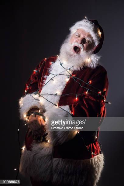sleepy santa yawning tied up / tangled in christmas lights - pere noel libre de droit photos et images de collection