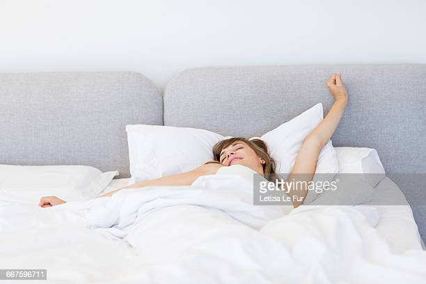 Sleepy woman waking up and yawning with a stretch