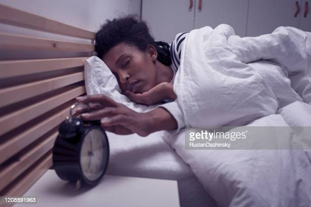 donna assonna che si sveglia, spegne la sveglia. - colpire foto e immagini stock