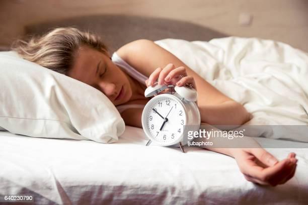 Verschlafene Junge Frau im Bett und Wecker Verlängerung um