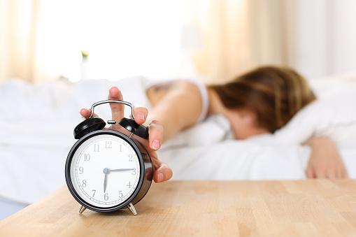 Sleepy young woman trying kill alarm clock 490474430