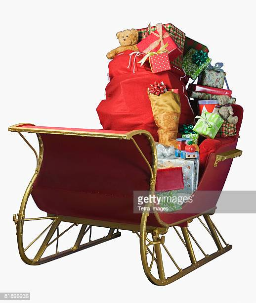 sleigh with bag of christmas toys - sleigh stock photos and pictures