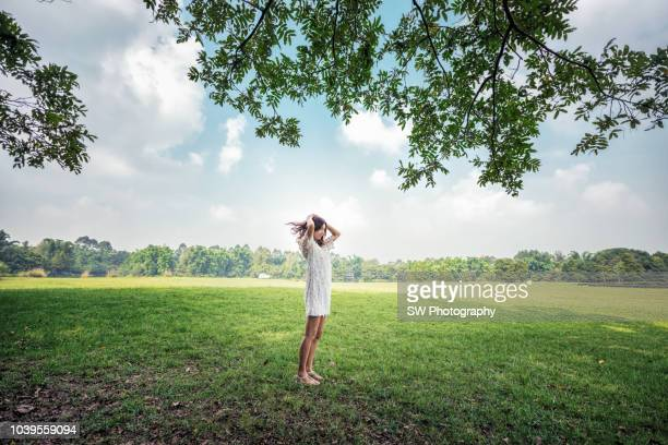 slender chinese woman standing in the meadow - public park stock pictures, royalty-free photos & images