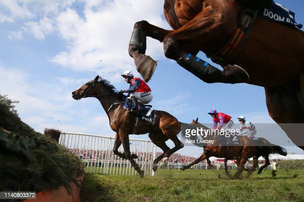 Slevin riding Us And Them clears a fence in the Doom Bar Maghull Novices' Chase during the Grand National Day at Aintree Racecourse on April 06 2019...