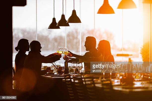 slhouette of a group of friends toasting during lunch time in a high-end restaurant - after work stock photos and pictures