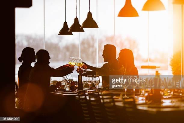 Slhouette von einer Gruppe von Freunden während der Mittagspause in einem edlen Restaurant Toasten