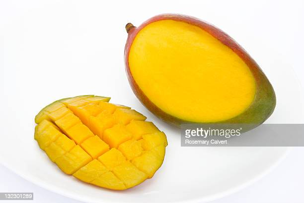 Slice cut from a juicy, ripe mango ready to eat.