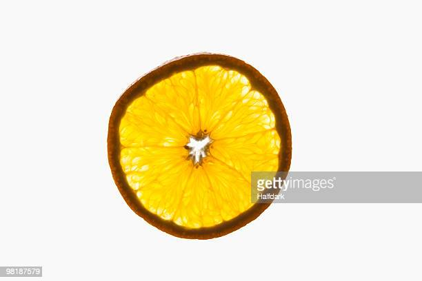 A slice of an organic orange on a lightbox