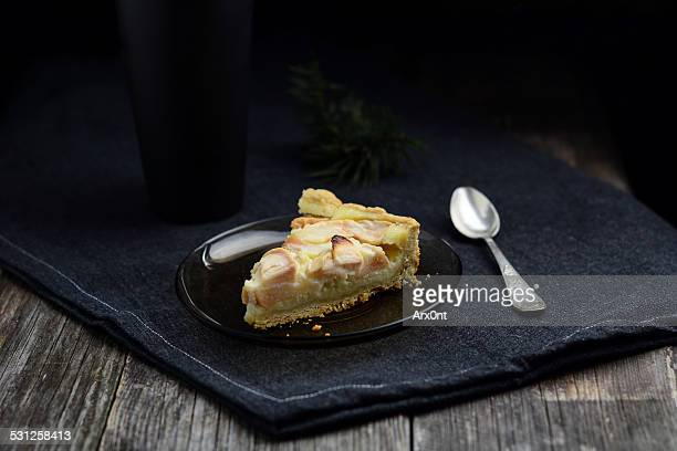 Slice of apple pie on black background