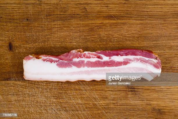 Slice of bacon on wooden cutting board