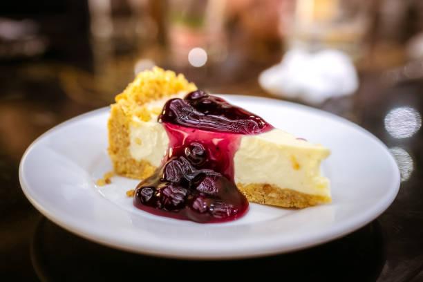 slice of blueberry cheesecake on a plate - 餐後甜品 個照片及圖片檔